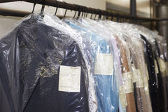 Dry cleaning things hanging in a row Royalty Free Stock Photos