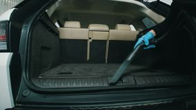 Dry cleaning of trunk, man cleans the car interior with vacuum cleaner. Close up stock video footage