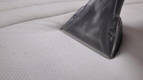 Dry cleaning of the white mattress. Cleaning company cleans the mattress