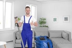 Dry cleaning worker with professional apparatus. Indoors Stock Photography