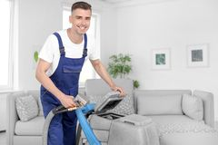 Dry cleaning worker with professional apparatus. Indoors Stock Image
