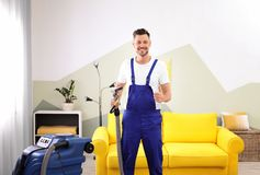 Dry cleaning worker with professional apparatus. Indoors Royalty Free Stock Image