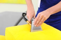 Dry cleaning worker removing dirt from sofa cushion. Indoors royalty free stock photo