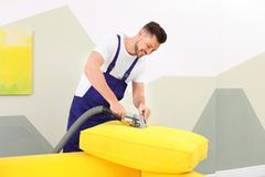 Dry cleaning worker removing dirt from sofa cushion. Indoors royalty free stock images