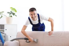 Dry cleaning worker removing dirt from sofa. Indoors Stock Photos