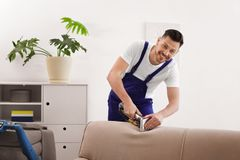 Dry cleaning worker removing dirt from sofa. Indoors Stock Image