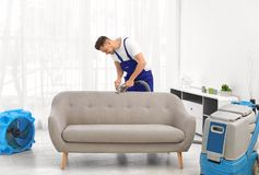 Dry cleaning worker removing dirt from sofa. Indoors royalty free stock image