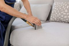 Dry cleaning worker removing dirt from sofa. Indoors Stock Photography