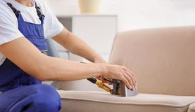 Dry cleaning worker removing dirt from sofa indoors. Dry cleaning male worker removing dirt from sofa indoors Stock Images