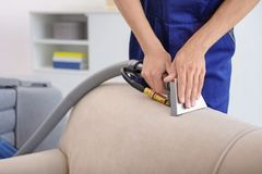 Dry cleaning worker removing dirt from sofa. Indoors Stock Images