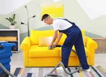 Dry cleaning worker removing dirt from sofa. Indoors Royalty Free Stock Images
