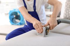 Dry cleaning worker removing dirt from sofa. Indoors Royalty Free Stock Photos