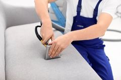 Dry cleaning worker removing dirt from sofa. Indoors Stock Photo