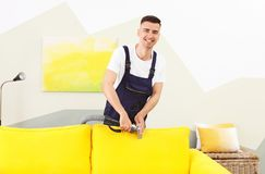 Dry cleaning worker removing dirt from sofa. Indoors Royalty Free Stock Photo