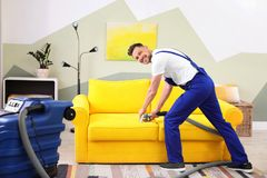 Dry cleaning worker removing dirt from sofa. Indoors Royalty Free Stock Photography