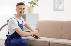 Dry cleaning worker removing dirt from sofa ndoors. Dry cleaning worker removing dirt from sofa indoors Stock Photos