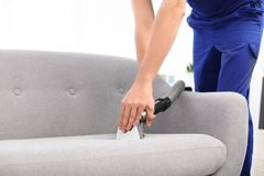Dry cleaning worker removing dirt from sofa in room. Dry cleaning worker removing dirt from sofa indoors Royalty Free Stock Photography