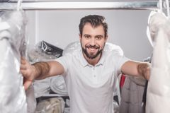 Dry cleaning worker at warehouse with clothing packed. In plastic bags Stock Photos