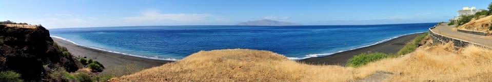 Dry cliff splits the black sand beach Stock Photo