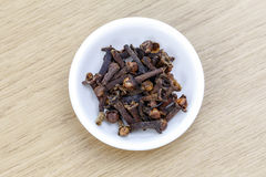 Dry clove in white bowl on wooden table. The dry clove in white bowl on wooden table royalty free stock image
