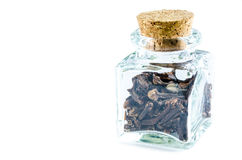 Dry cloves in glass bottle isolated on white background. Stock Image
