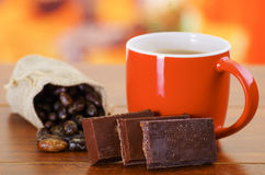 Dry cocoa bean in a small sack and a cup of chocolate over a wooden background Stock Images