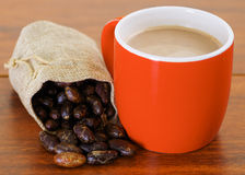 Dry cocoa bean in a small sack and a cup of chocolate over a wooden background Royalty Free Stock Photo