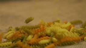Dry colored pasta pouring on grey sack, advertising of healthy food production. Stock footage stock footage