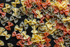 Dry coloured farfalle pasta on black textured wood from above. A Stock Photography