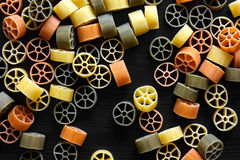 Dry coloured wagon wheel pasta on black textured wood, from abov Stock Photo