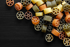 Dry coloured wagon wheel pasta on black textured wood, from abov Stock Images