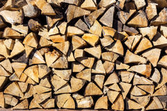 Dry conifer firewood in sunlight. Yellow dry chopped conifer firewood logs background in a pile outdoor in sunlight royalty free stock photo