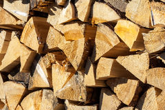 Dry conifer firewood in sunlight. Yellow dry chopped conifer firewood logs background in a pile outdoor in sunlight royalty free stock image