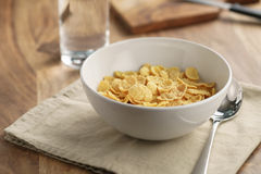 Dry corn flakes for breakfast in bowl on table Stock Photo