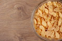 Dry corn flakes in a glass bowl on the table. Stock Photo