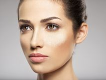 Dry cosmetic makeup powder is on the female face. Beauty treatment concept. Girl makes makeup stock photo