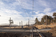 Dry Countryside with Rural Gravel Road Crossing Railway Tracks Royalty Free Stock Image