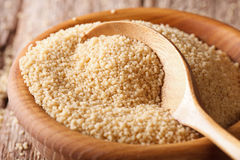 Dry couscous in a wooden bowl with a spoon macro. horizontal Royalty Free Stock Images