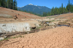 Dry cracked bed of the river during drought, mountain in distance Stock Photos