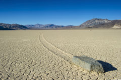 Dry cracked desert showing mysterious wandering rock, the racetr. Barren vista of The Racetrack at Death Valley National park showing one of the mysterious Stock Images