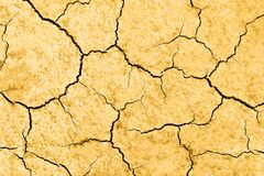 Dry cracked earth. Waterless planet. Dry yellow cracked earth. Hot climate and drought concept. Desert background stock photography