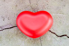 Dry cracked ground background with a red heart Stock Photo