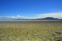 Dry, cracked lakebed stretching to horizon. A dry, cracked lakebed stretches off toward mountains and clouds on the horizon near Syracuse, Utah Stock Images