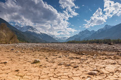Dry cracked river earth ground and blue sky. Dry cracked earth ground with stones in mountain land at blue sky royalty free stock image