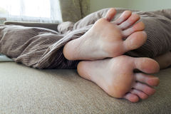Dry cracked skin of woman feet in bed. Foot treatment. Royalty Free Stock Photos