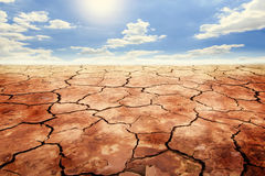 Dry cracked soil in drought land under blue sky. Stock Photos