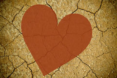 Dry cracked texture background with a red heart Royalty Free Stock Photo