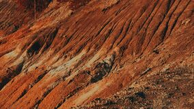 Dry, cracked, uneven, red soil, reminiscent of the Martian red landscape.
