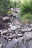Dry Creek Design. A custom designed dry creek is a feature of this perennial backyard garden royalty free stock images