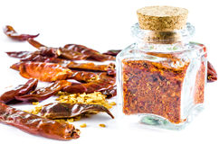 Dry crushed chili  in glass bottle and whole chili pods and seed Stock Image